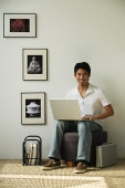 Young man with laptop on lap looking at camera - Asia Images Group