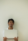 Young man with laptop on hands smiling at camera - Asia Images Group