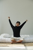 Young man sitting on bed, stretching arms - Asia Images Group