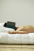 Young man lying in bed, face covered by a book - Asia Images Group