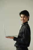 Young man with laptop on one hand smiling at camera - Asia Images Group