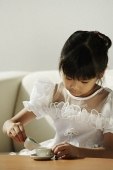 Girl in white dress playing with tea cups - Asia Images Group
