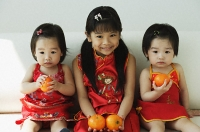 Girls with mandarin oranges sitting on sofa - Asia Images Group