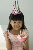 Birthday girl with cupcake and spoon on hand smiling at camera - Asia Images Group