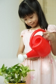 Girl watering plant - Asia Images Group