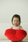 Baby girl with heart-shaped cushion - Asia Images Group