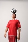Soccer player with ball on head - Asia Images Group