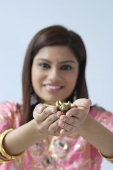 Indian woman holding candle in cow-shaped holder - Asia Images Group