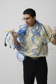 Frustrated man with computer cords and wires - Asia Images Group