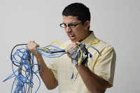Frustrated man with tangled wires - Asia Images Group