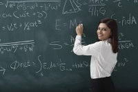 Woman writing equations on chalk board - Asia Images Group