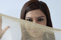 Young woman hiding behind veil - Asia Images Group