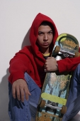 young man wearing red hooded sweatshirt holding skateboard - Asia Images Group