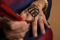 hands of Indian woman applying henna - Asia Images Group