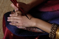 Indian woman painting hand with henna - Asia Images Group
