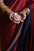 Indian woman offering sweets - Asia Images Group