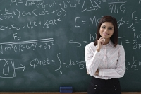 Woman standing proudly in front of chalk board - Asia Images Group