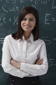 Teacher leaning against chalk board - Asia Images Group
