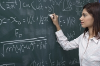 Woman working on equations on chalk board - Asia Images Group