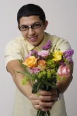 Young man holding bouquet of flowers - Asia Images Group