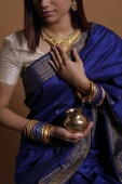 Indian woman wearing sari and holding offering - Asia Images Group