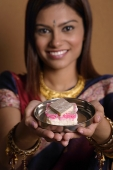 Indian woman offering plate of sweets - Asia Images Group