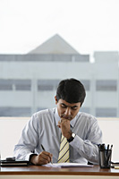 business man writing at his work desk - Asia Images Group