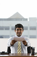 business man handing over a stack of paper - Asia Images Group
