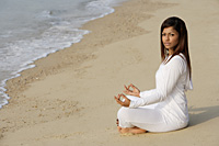 woman practicing yoga at the beach - Asia Images Group