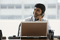 business man talking on office phone - Asia Images Group