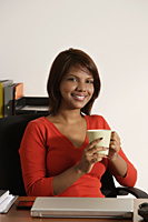 Business woman holding coffee mug, smiling at camera - Asia Images Group