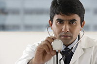 doctor holding up stethoscope - Asia Images Group