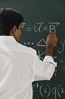 teacher writing formulas on chalkboard - Asia Images Group