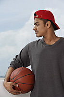 young man with red cap, holding basketball - Asia Images Group