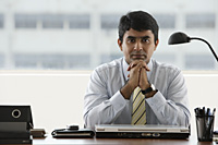 business man resting chin in folded hands - Asia Images Group