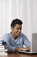young man using laptop at his desk - Asia Images Group
