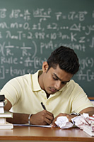 young man sitting at his desk, writing - Asia Images Group