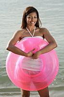 woman at beach with pink tube - Asia Images Group