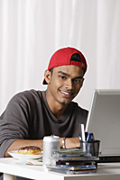 young man with red cap working on laptop at desk - Asia Images Group