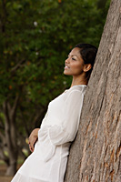 woman leaning on tree, looking away - Asia Images Group