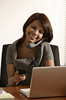 Business woman talking on the phone, looking at laptop and mobile device. - Asia Images Group
