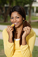 woman eating orange outside - Asia Images Group