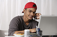 young man with red cap, talking on phone and working on laptop - Asia Images Group
