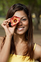 woman covering an eye with flower, smiling - Asia Images Group