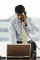 business man standing, using laptop while on phone - Asia Images Group