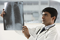 indian doctor holding up x-ray scan - Asia Images Group