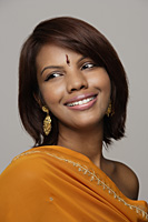 Woman wearing orange sari and bindi smiling - Asia Images Group