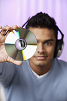 young man with headphones on, holding compact disc in front of him - Asia Images Group