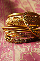 gold Indian bangles on pink sari cloth - Asia Images Group