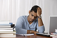 young man studying at his desk, stressed - Asia Images Group